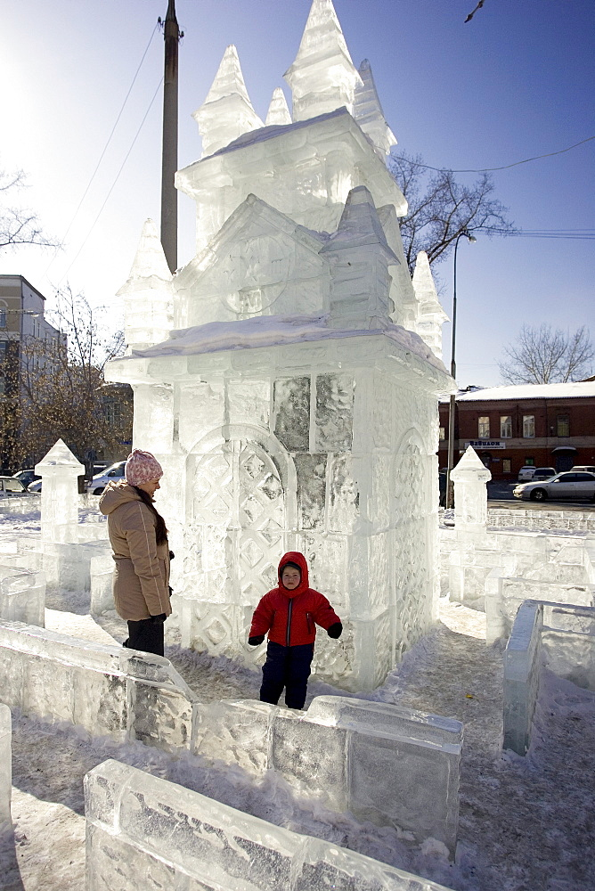 A woman and child playing in an ice playground in the winter in Irkutsk, Siberia, Russia.