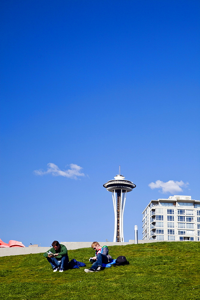 SEATTLE, WASHINGTON, USA. Two men sit on a lawn with the space needle in the background in downtown Seattle.
