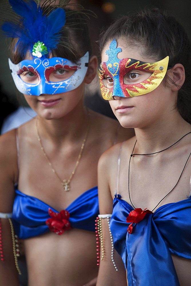 A couple of girls wearing masks during the traditional carnaval in Colonia del Sacramento, Uruguay.