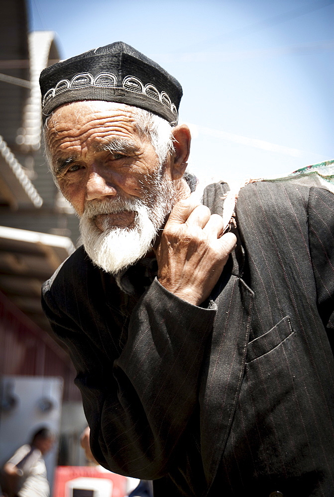 Old man carrying goods in the Osh street market of Kyrgyzstan