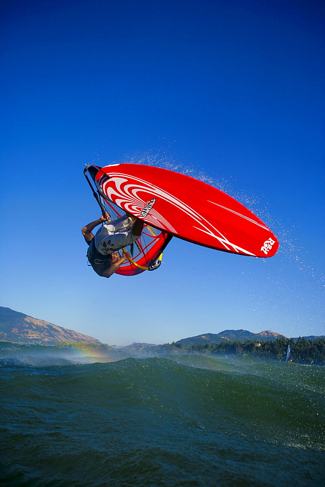 Windsurfer lofts a beautiful forward loop over the middle of the Columbia River Gorge.