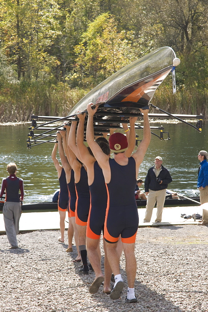 Members of the men's crew team at Hobart College carry their 8 man shell above their heads toward the water at the Hobart Crew Ragata, in Geneva, New York.