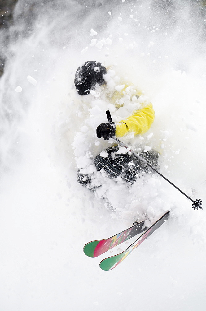 A skier is engulfed in a thick cloud of powder as he makes a sharp turn in deep snow  while skiing a mountain in British Columbia, Canada.