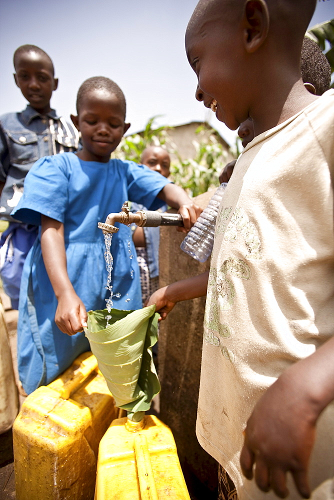 Girls filling water bottles at Rwandan village well.
