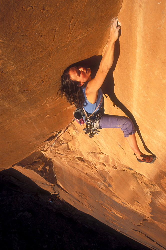 Woman rock climbing on Tombstone, Moab, UT