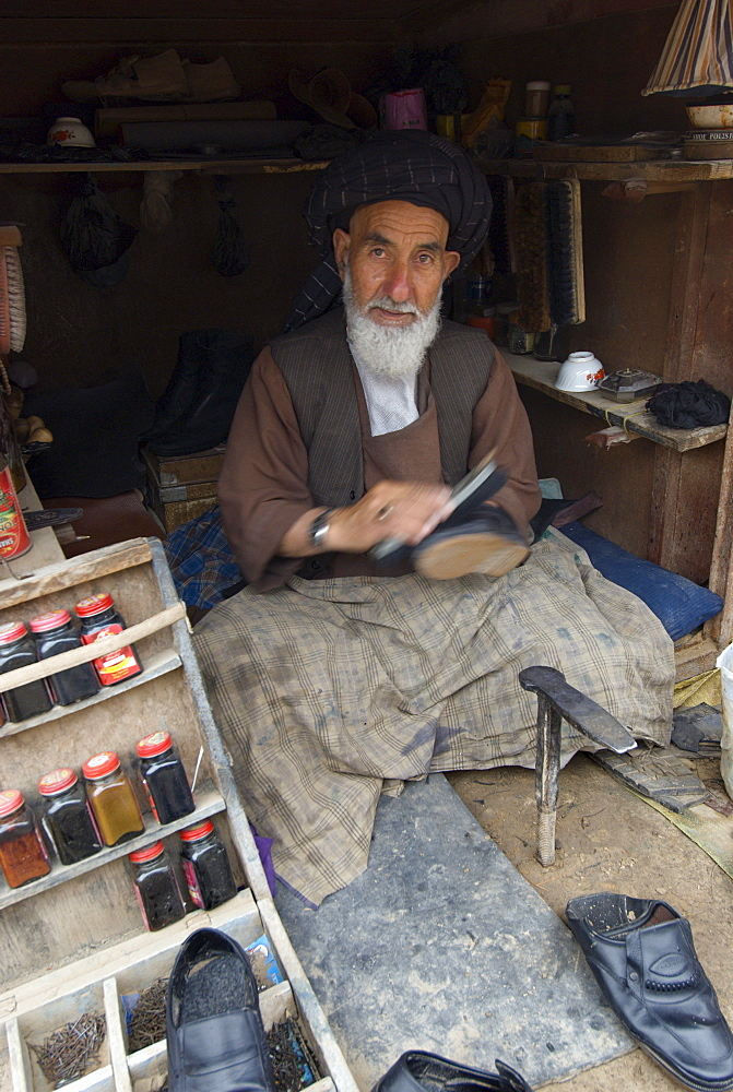A Tajik man repairs and shines shoes in the bazaar of  Turghondi, a town on the border with Turkmenistan, in the northern part of Herat Province.