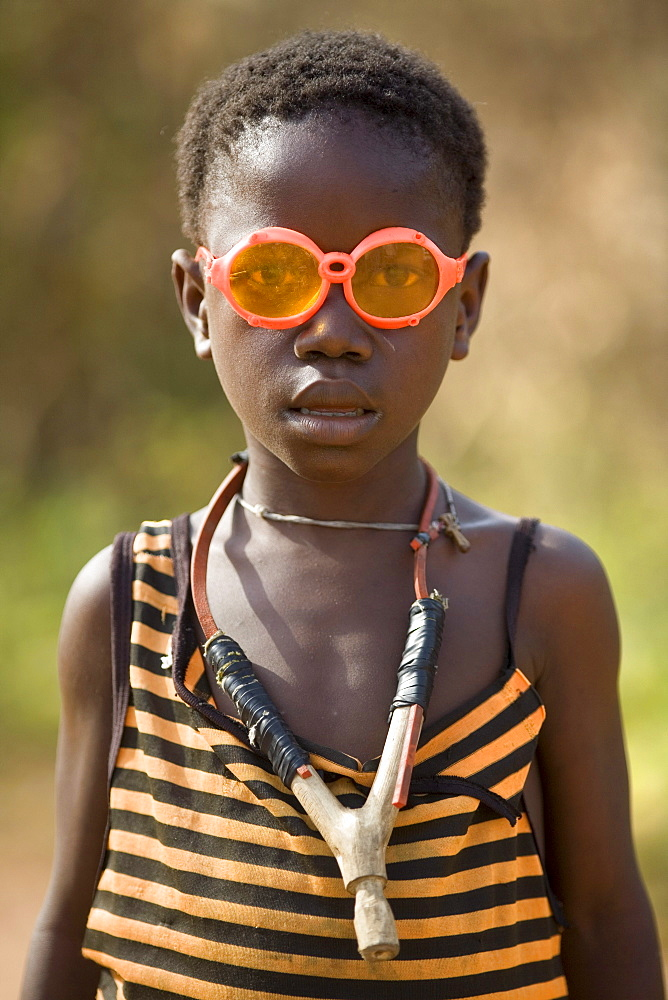 Portrait of a young boy wearing bright orange glasses and a sling shot around his neck. Gbolokai is a small town of a few hundred people 20 minutes off the main road near Totota, all of its inhabitants fled during the long brutal civil war and have slowly returned after 2005 to try and rebuild their lives.