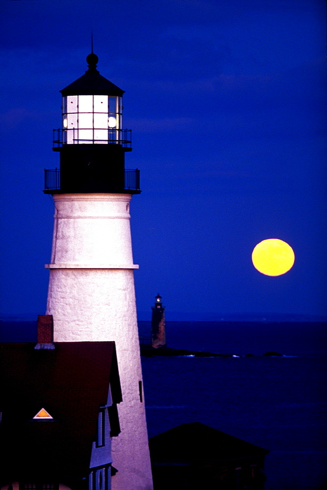 The full moon rises near the Portland Headlight on December 22, 1999 in Cape Elizabeth, Maine.