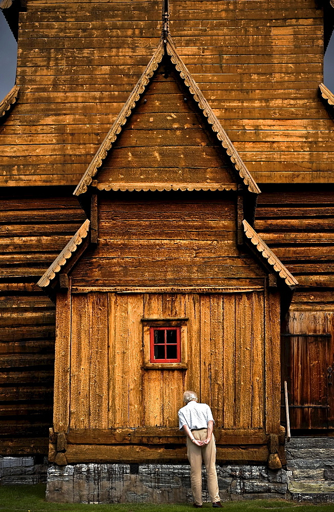 A man inspects the side of View of the exterior of Lom Stavkyrkje in Lom, Norway.