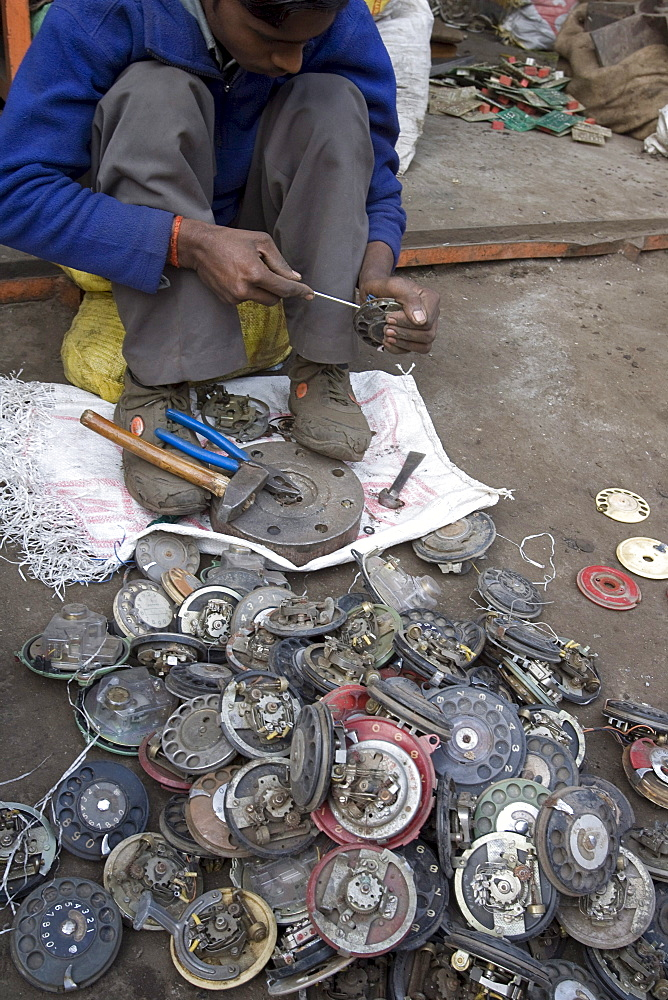 At a scrap metal market in New Delhi, India old rotary phone are disassembled for the metals.