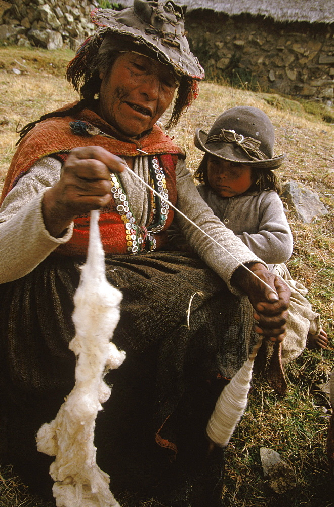 Elderly Quechua woman spins wool while her granddaughter looks on in Puma Chanca.