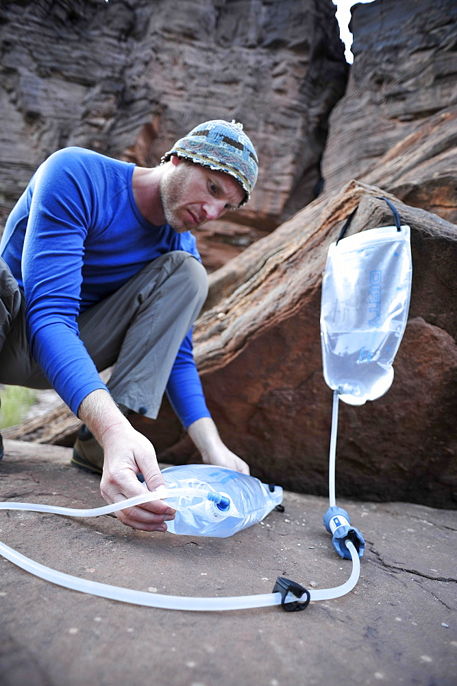 Male hiker filters water on a cliff-pinched patio near Deer Creek Falls in the Grand Canyon outside of Fredonia, Arizona November 2011.  The 21.4-mile loop starts at the Bill Hall trailhead on the North Rim and descends 2000-feet in 2.5-miles through Coconino Sandstone to the level Esplanada then descends further into the lower canyon through a break in the 400-foot-tall Redwall to access Surprise Valley.  Hikers connect Thunder River and Tapeats Creek to a route along the Colorado River and climb out Deer Creek.