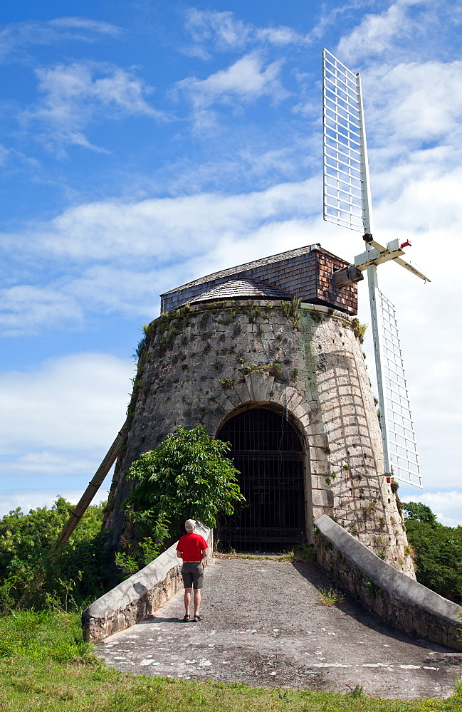 Visitor (man) looks at the remains of a windmill that powered the sugar cane operation at Estate Whim at Frederiksted, St. Croix.