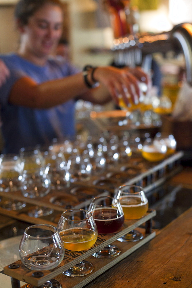 Bartender pours beers for tasting at Allagash Brewery