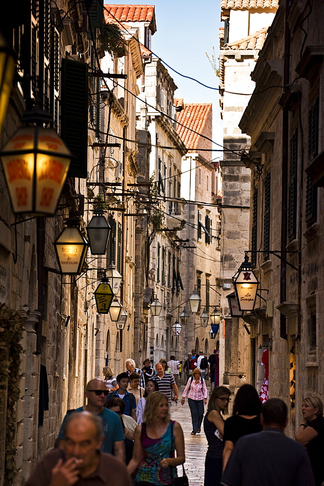 People walk down a narrow street in Dubrovnik.