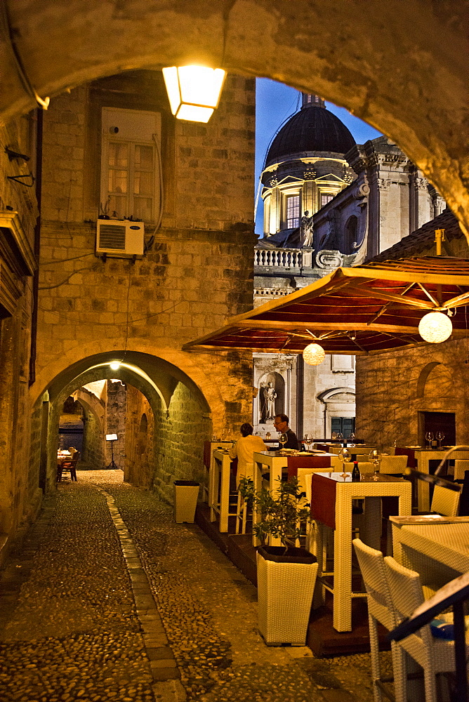 Restaurant tables are lit up at dusk in an alley in Dubrovnik, Croatia.