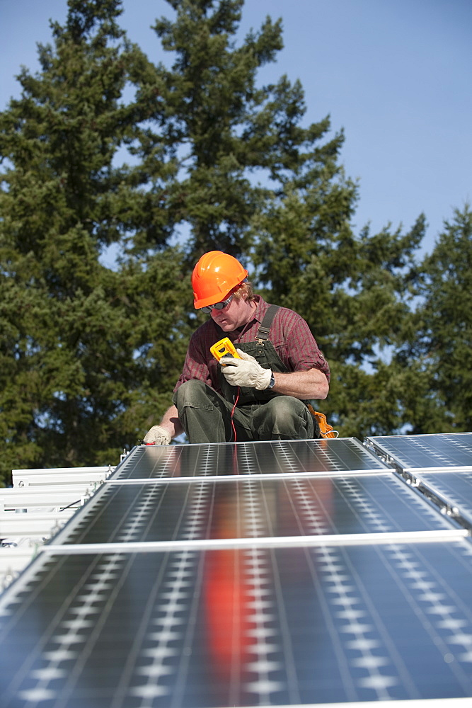 A technician measures the electricity generated by a photovoltaic panel, United States of America