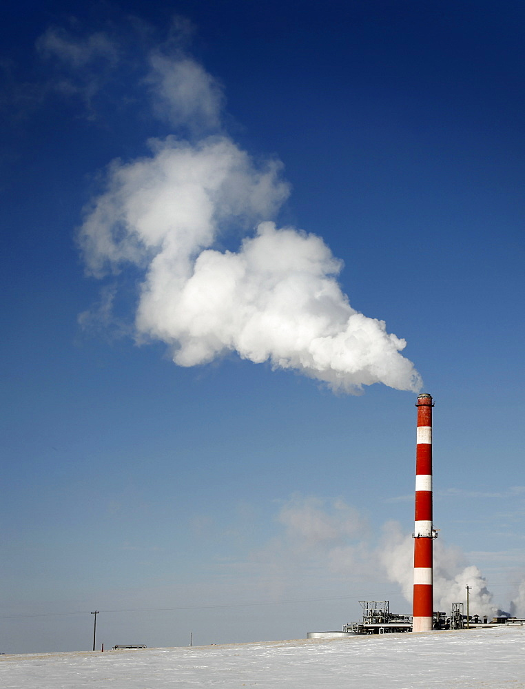 Smoke and steam raises from a smoke stack on a clear blue sky day, CANADA