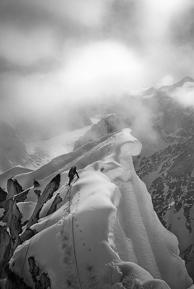 CJ Pearson navigates the knife-edged and corniced ridge of Peak 11,300 in the Alaska Range, United States of America