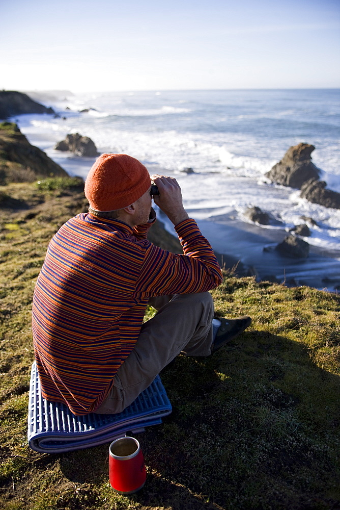 Surfer checking the waves with binoculars from a cliff
