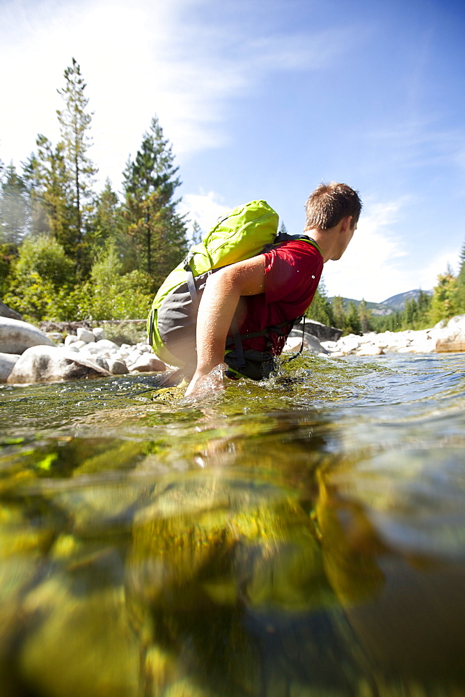 Young adult man fording a deep section of a river wearing a day pack