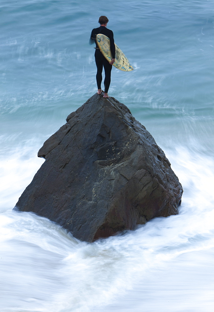 Adult male surfer standing atop a rock on the beach with water blurring around the rock