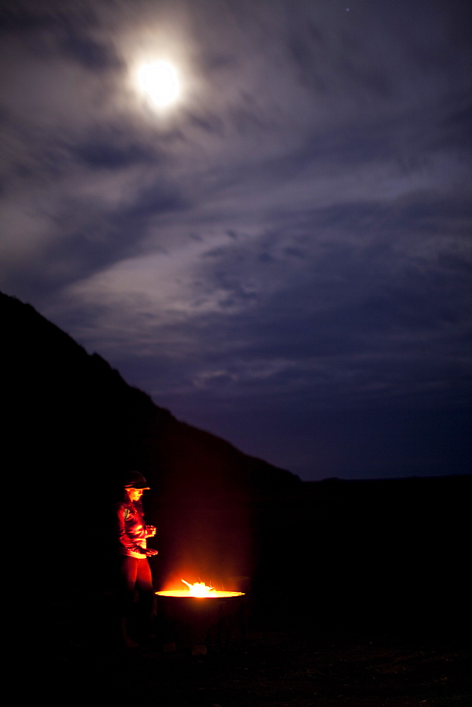 Woman standing by a glowing fire on a moody night.