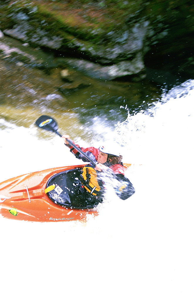 Kayaker takes a drop over a small waterfall on Cow Creek, northern Idaho. (blurred motion)