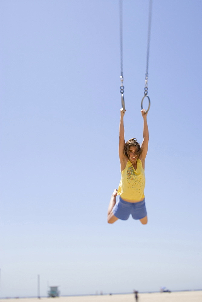 girl having Fun at the beach using the gymnastic rings.