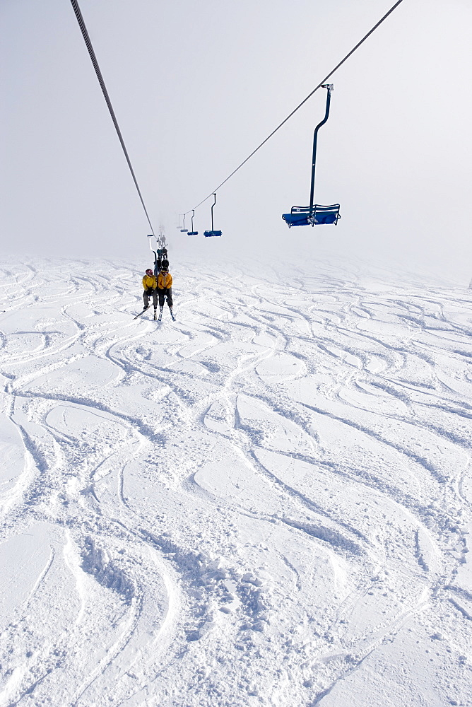 People riding up a chairlift to go sking