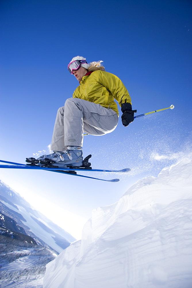 Woman skiing off cornice