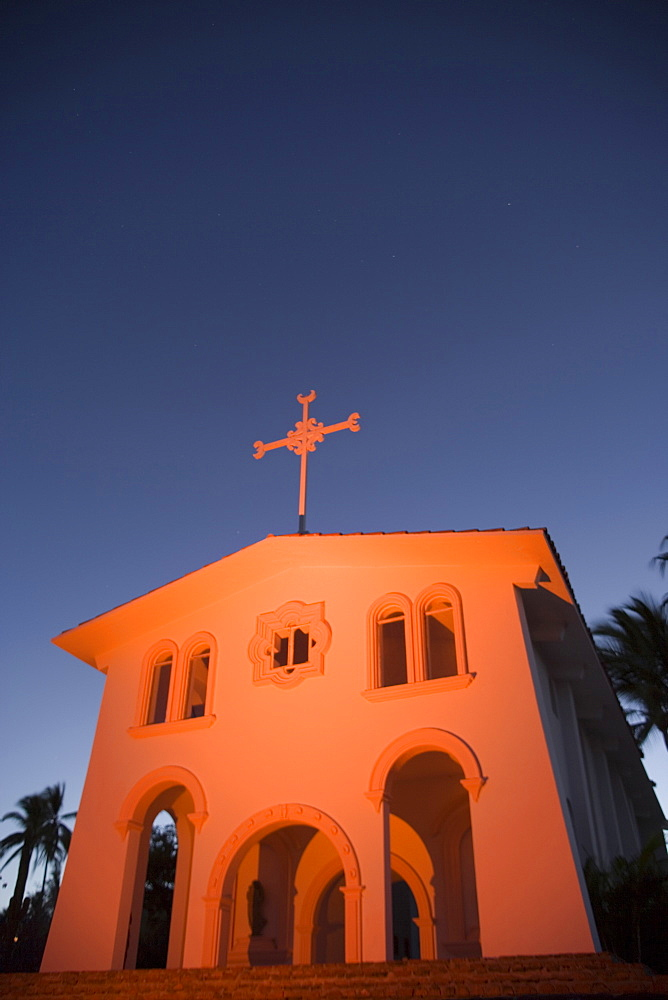 An old church glowing orange in the twilight
