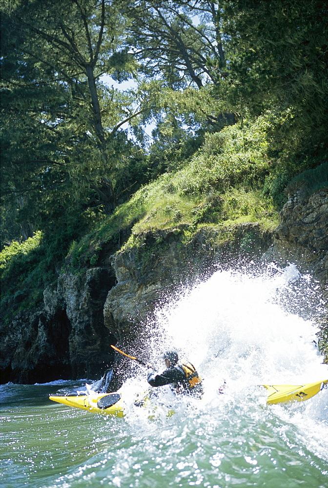 Sea kayaker paddling through an ocean wave