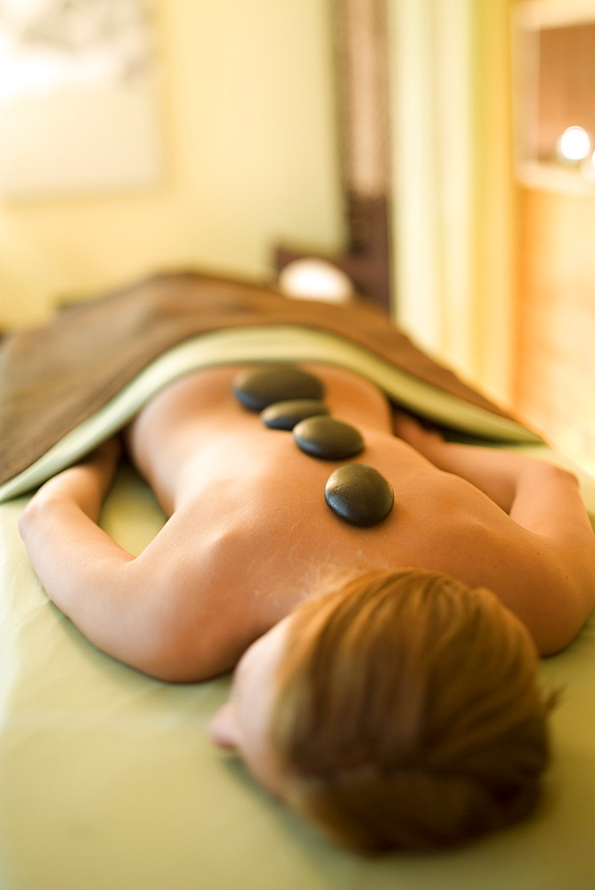 A woman receives a hot rock treatment in in Sandpoint, Idaho.