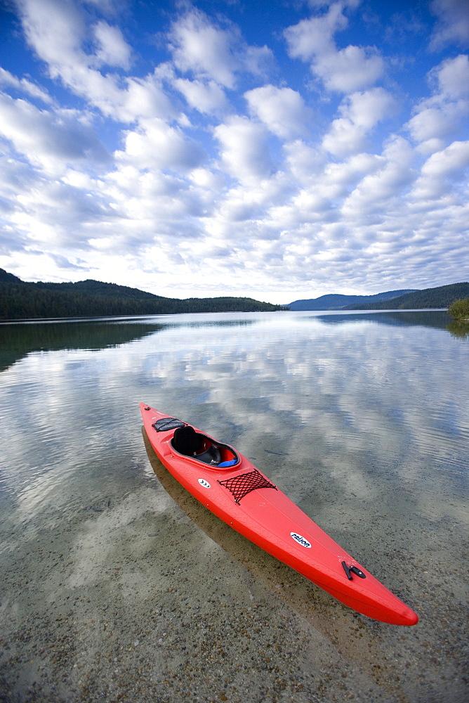 Red sea kayak floating on still lake.