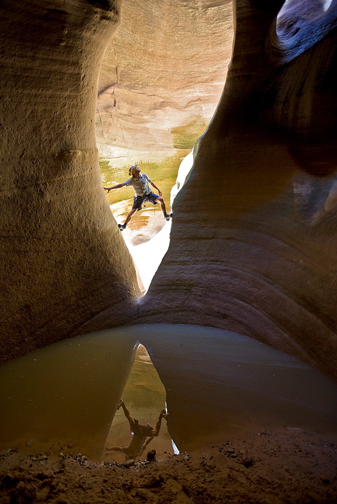 Man stemming between two walls in canyon above pool, Zion National Park, Utah.