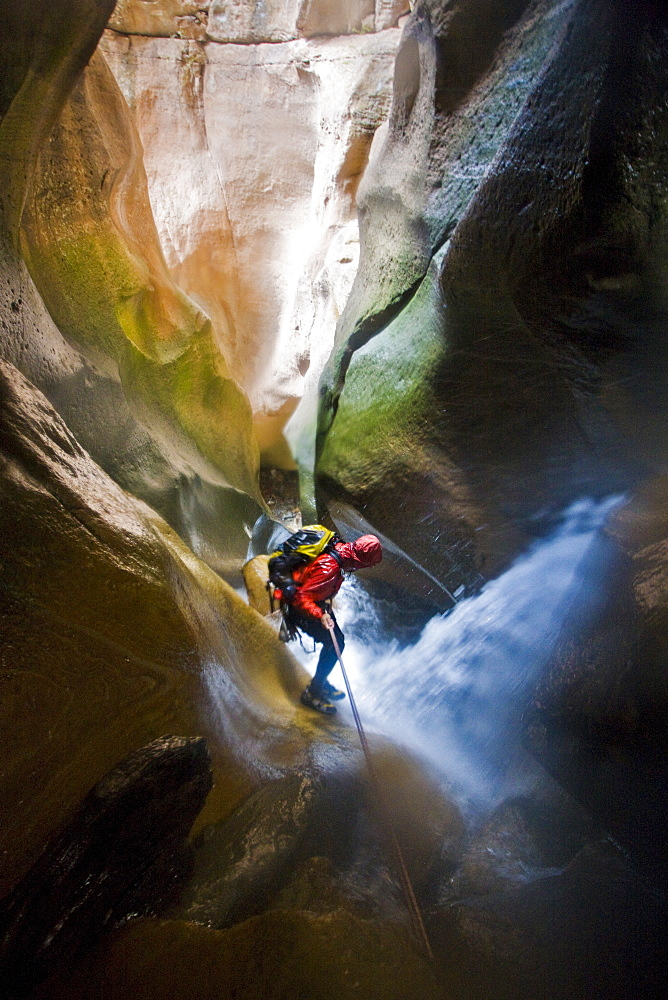 Man rappelling down canyon through waterfall in Utah.