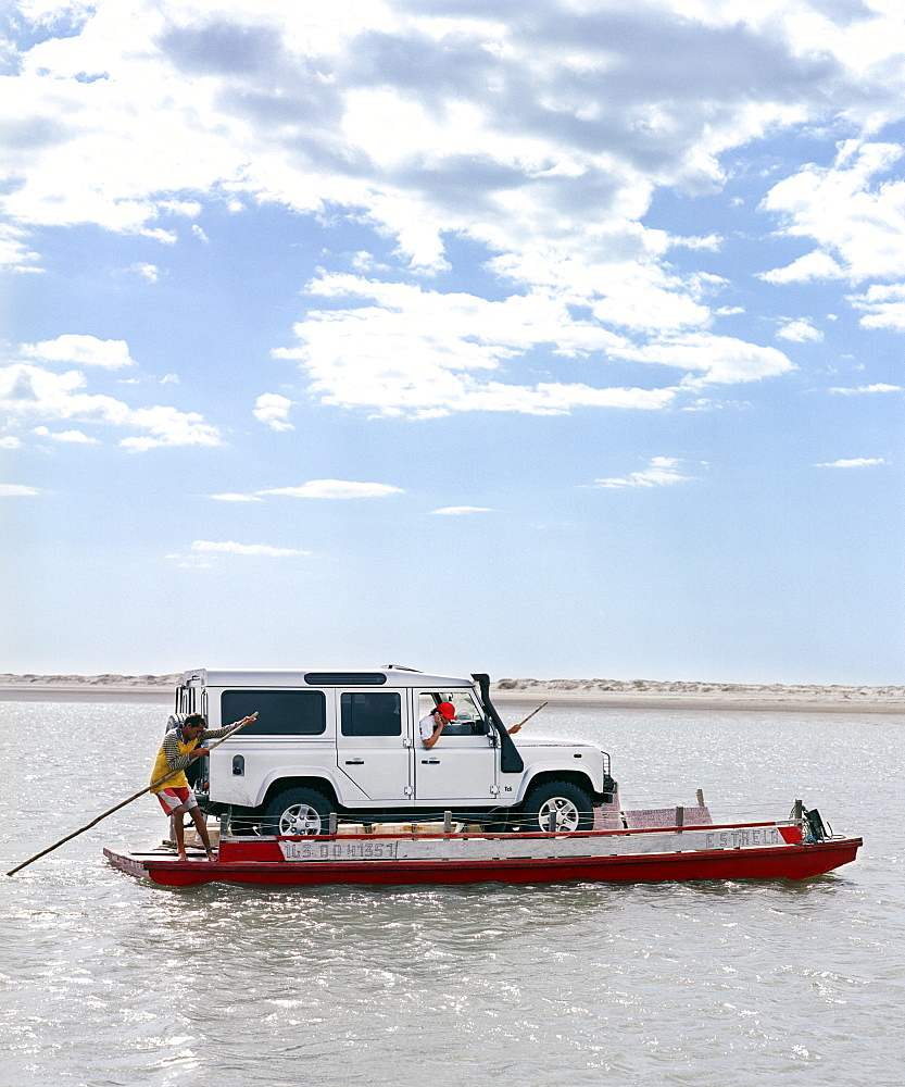 A ferryboat operator brings a Land Rover across a river.