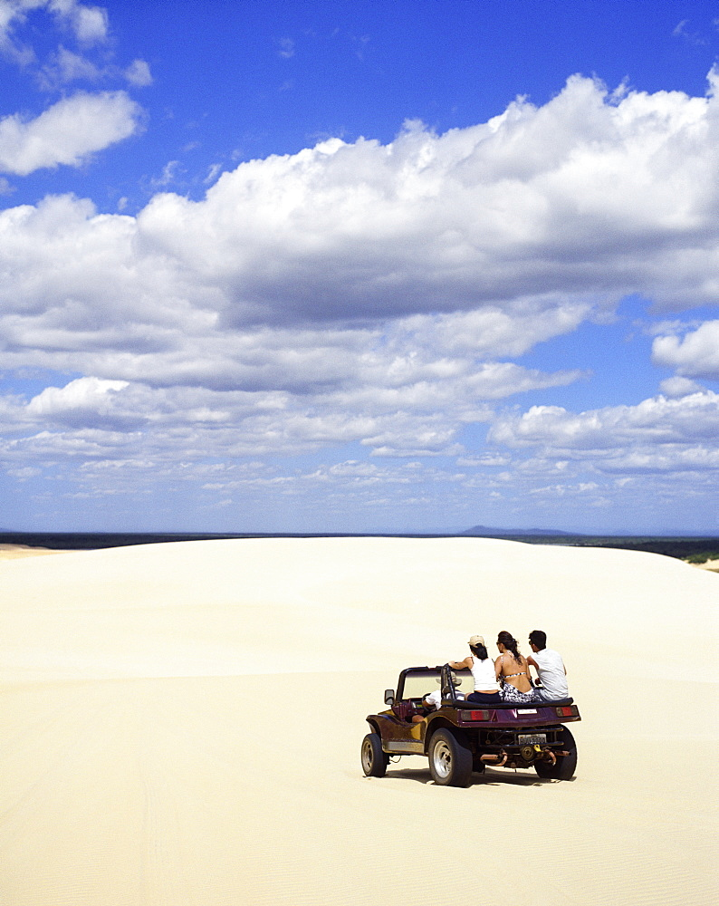 A group of friends drive a dune buggy across the sand.