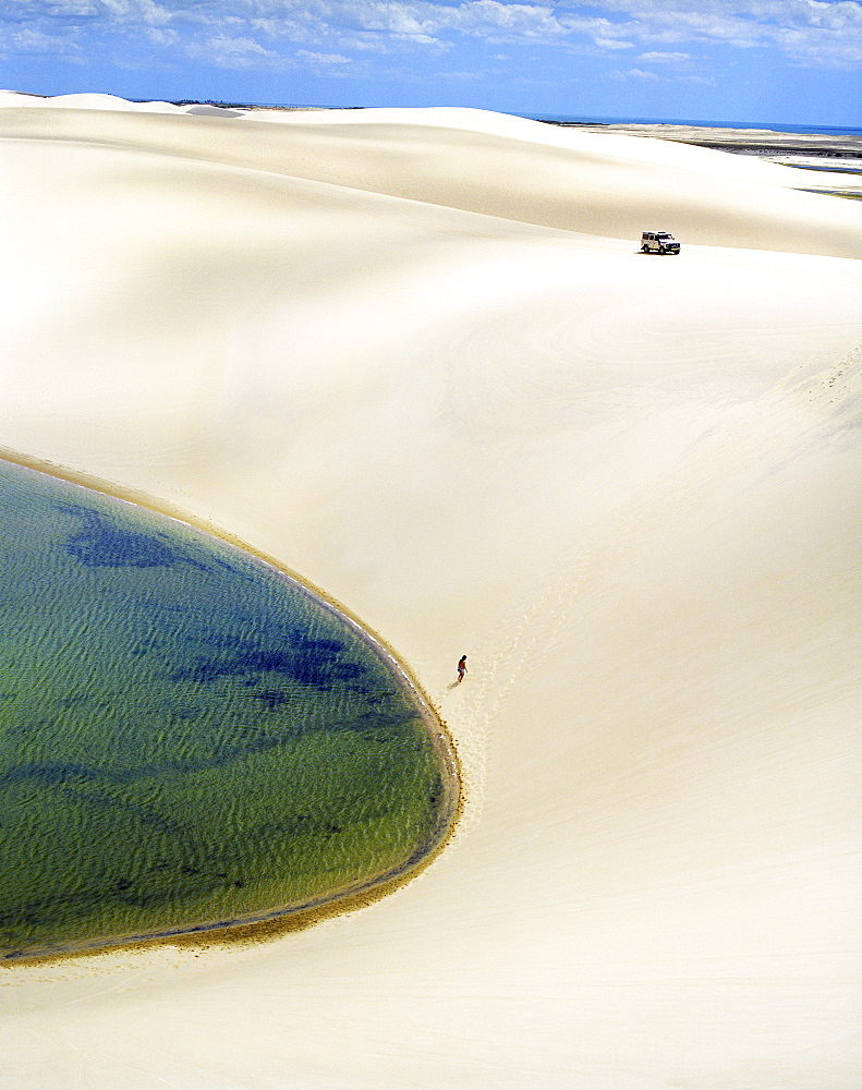 A sand boarder hikes back up a dune.