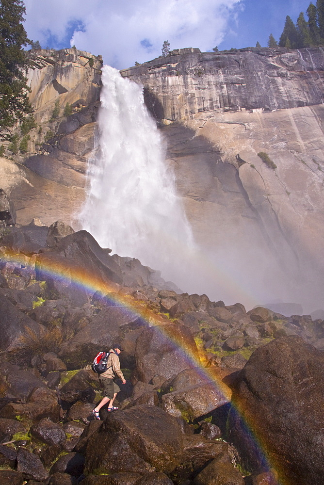 A man hiking in Yosemite National Park by Nevada Falls in California.