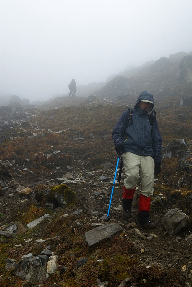 Surrounded by fog, two men descend a rocky slope in mountains of Butan.