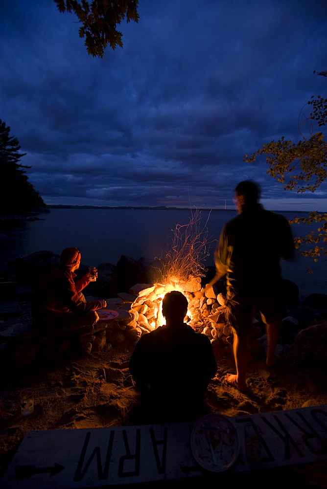 Three adult men sitting around a campfire at night.