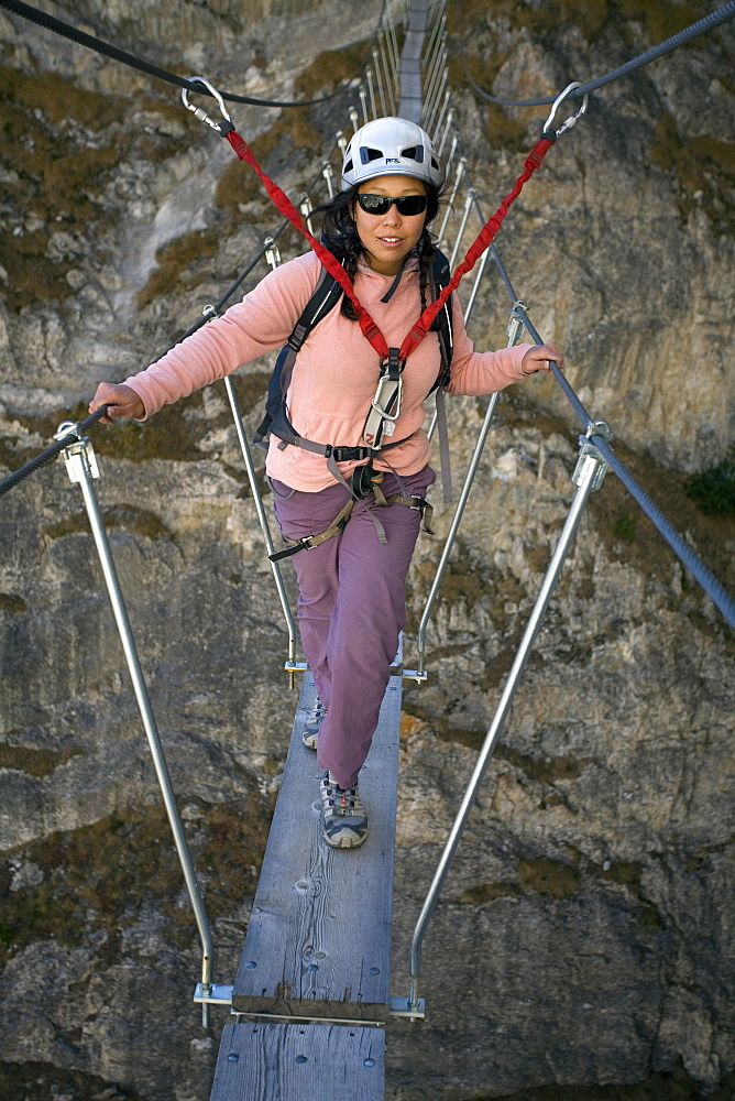 A young woman walking on a bridge while engaging in the sport of Via Ferrata in Val D'isere, Savoie, France.