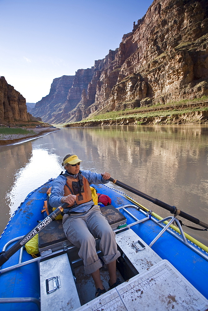A woman rowing an inflatable raft down the Colorado river, Utah.