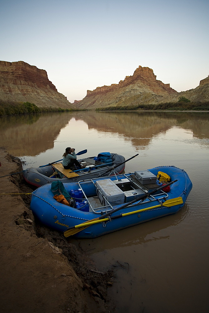 Woman sitting in a raft looking out with binoculars, Colorado river, Canyonlands National Park, Utah.