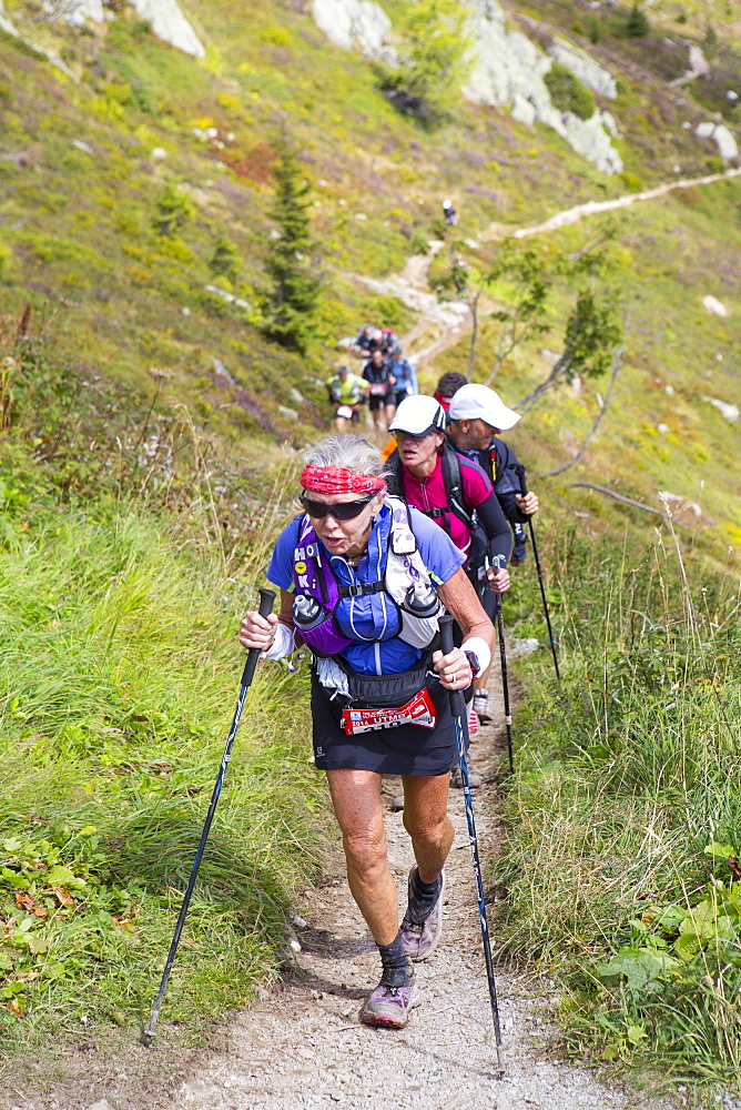 An elderly woman is running in the hills of Chamonix. She is close to finishing the extremely exhausting UTMB race. The Ultra-Trail du Mont-Blanc (also referred to as UTMB) is a single-stage mountain ultramarathon. It takes place once a year in the Alps, across France, Italy and Switzerland. The distance is approximately 166 kilometres (103 mi), with a total elevation gain of around 9,600 m. It is widely regarded as one of the most difficult foot races in Europe. It's certainly one of the largest with over two thousand starters. The combined participation in all of the events is approaching 10 thousand runners. While the best runners complete the loop in slightly more than 20 hours, most runners take 30 to 45 hours to reach the finish line.