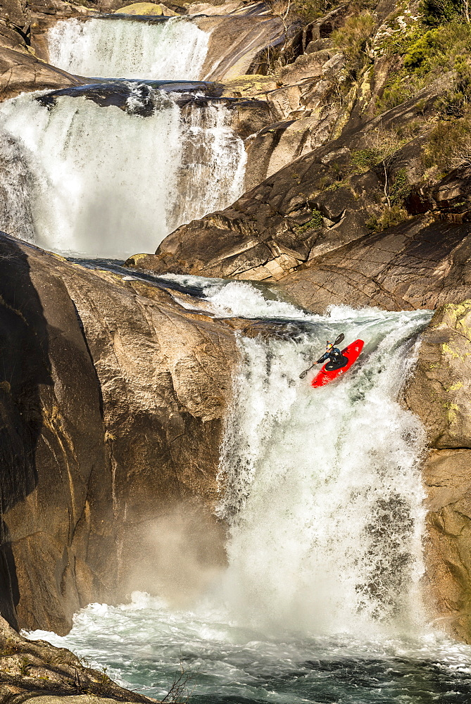 Spanish whitewater kayaker Aniol Serrasolses is dropping down the last waterfall of a triple set on the Rio Castro Laboreiro.