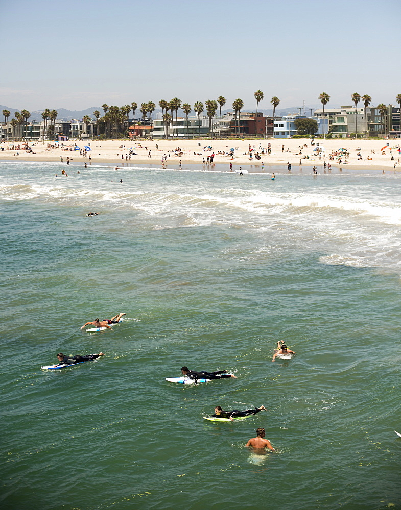 Surfers paddle out beyond the break while others relax in the sand on a sunny July 4, 2014 in Venice, Calif.
