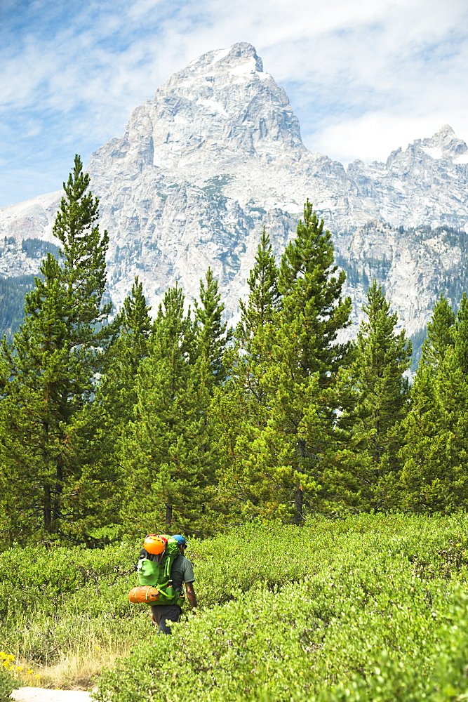 A Backpacker Hiking Toward The Grand Teton Mountains In Jackson Hole, Wyoming